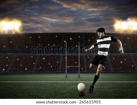 Rugby player in a black uniform kicking a ball on a stadium. - stock photo