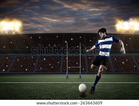 Rugby player in a blue uniform kicking a ball on a stadium. - stock photo