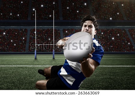 Rugby player in a blue uniform scoring on a stadium. - stock photo