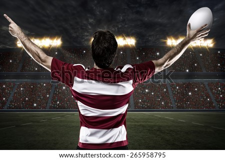 Rugby player in a red uniform celebrating on a stadium. - stock photo