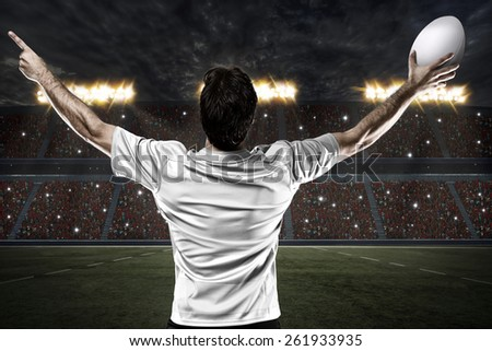 Rugby player in a white uniform celebrating on a stadium. - stock photo