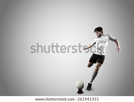 Rugby player in a white uniform kicking a ball on a white background. - stock photo