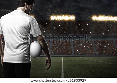 Rugby player in a white uniform on a stadium. - stock photo