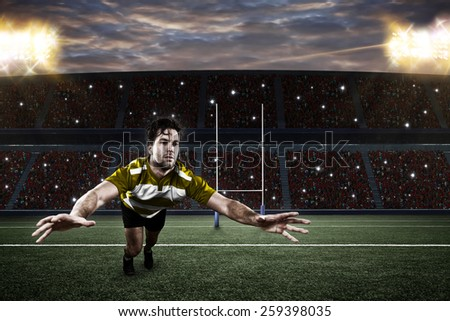 Rugby player in a yellow uniform giving a tackle on a stadium. - stock photo