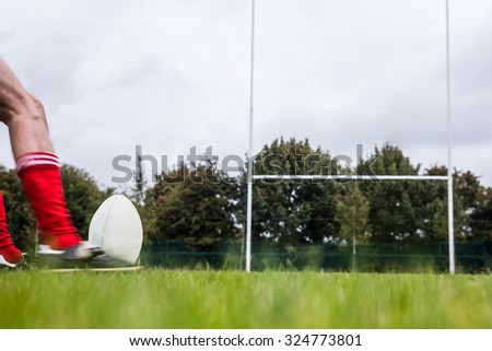 Rugby player kicking the ball at the park - stock photo