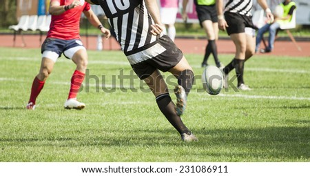 Rugby player kicking the oval ball - stock photo