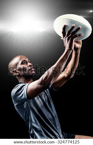 Rugby player looking up while throwing ball against spotlight