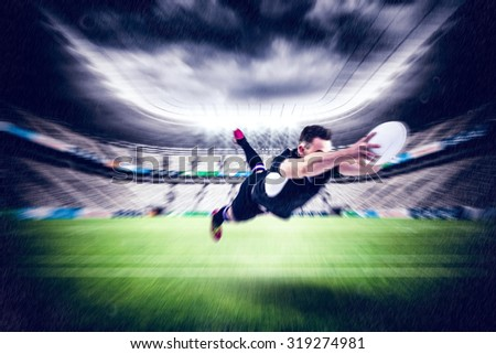 Rugby player scoring a try against rugby stadium - stock photo