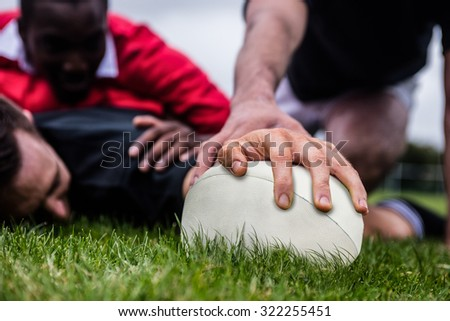 Rugby player scoring a try at the park - stock photo