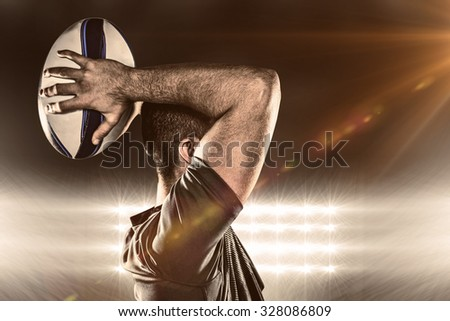 Rugby player throwing ball against spotlight - stock photo