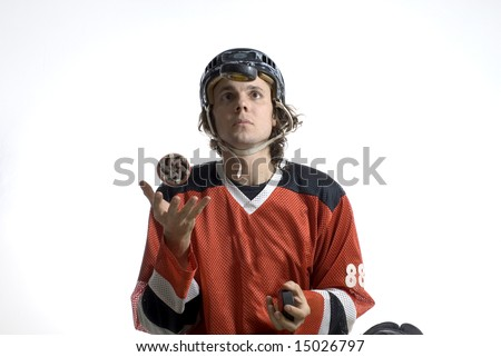 Rugby player wearing a helmet and uniform tosses a hockey puck in his hand. Horizontally framed photograph - stock photo