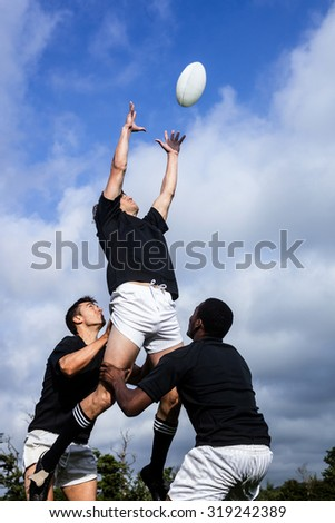 Rugby players jumping for line out at the park - stock photo