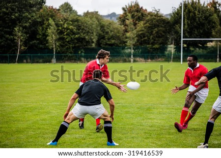 Rugby players passing during game at the park - stock photo