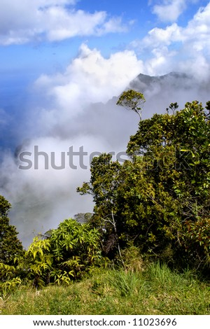 Rugged and beautiful Na Pali Coastline can be seen through the clouds at Na Pali overlook.  Vivid blue sky. - stock photo