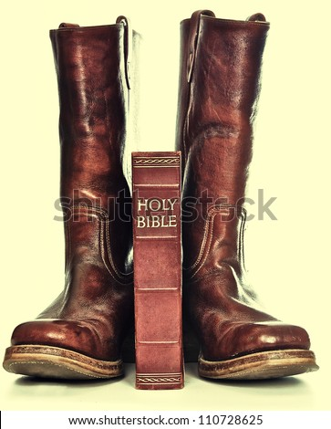 Rugged cowboy boots and bible - stock photo