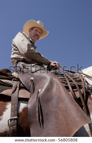 Rugged cowboy in the saddle. Focus on face. - stock photo