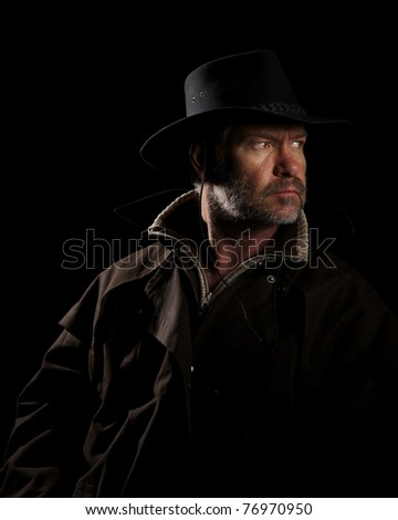 Rugged Cowboy on horseback looking intensely