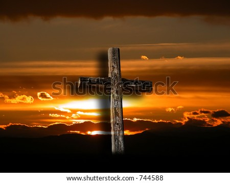 Rugged cross over an orange sunrise.