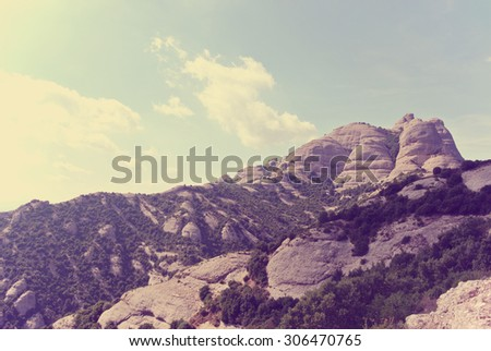 Rugged landscape of the Montserrat mountain, located close to Barcelona in Catalonia, Spain. Image toned in faded, washed out, retro, Instagram style with red filter and soft focus; vintage travel.