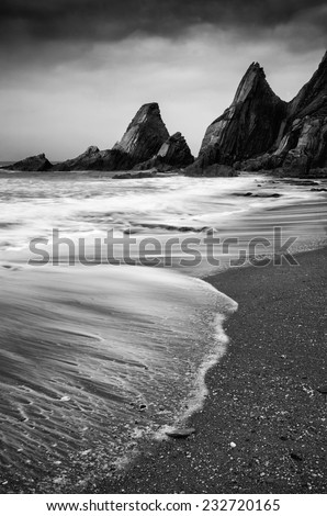 Rugged long exposure landscape seascape of rocky coastline  black and white - stock photo