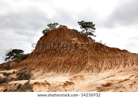 Rugged razor edged erosion in the sandstone on Torrey Pines hillside against cloudy sky - stock photo