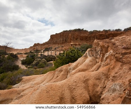 Rugged razor edged erosion in the sandstone on Torrey Pines hillside with sandstone bluff in the foreground - stock photo