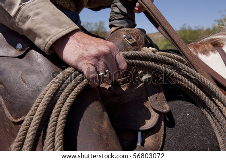 Rugged rodeo cowboy's hand with rope. Focus on hand. - stock photo