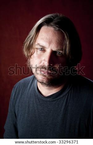 Rugged sad man with blue eyes and beard stubble - stock photo