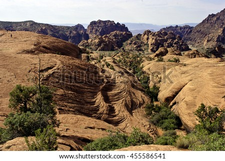 Rugged terrain near Zion, Utah, showing topography of ancient riverbed and hikers. - stock photo