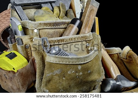Rugged worn carpenters leather work bags and belt with construction tools and hammer isolated on black and selective focus on plumb and rule - stock photo