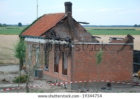 ruin of a damaged black family house after a fire - stock photo