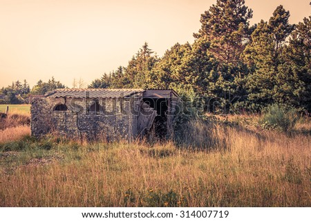 Ruin of a small brick house on a field - stock photo