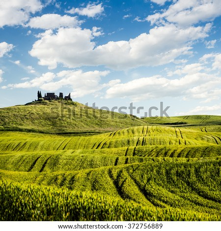 Ruin of the old castle behind the rolling hills with blue sky and white clouds