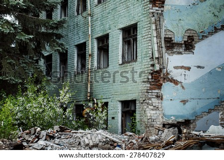 Ruined abandoned green bricks building with windows and fir trees at background. Concept of disaster, war. Mystic place with ghosts inside. - stock photo