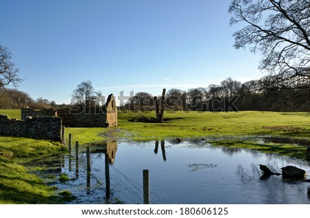Ruined barn in a flooded field - stock photo