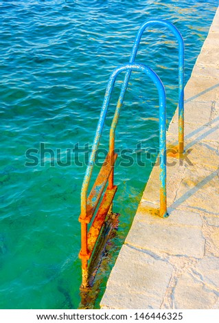 Ruined blue painted old iron made steps to the sea out of Nafplio city in Greece
