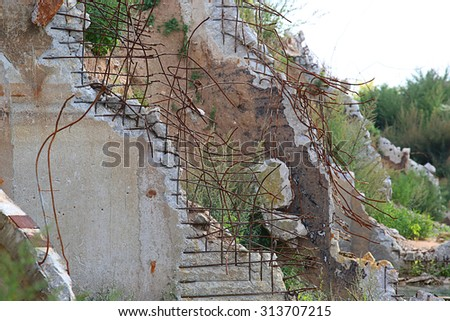 Ruined building of a factory with concrete hanging on armature - stock photo