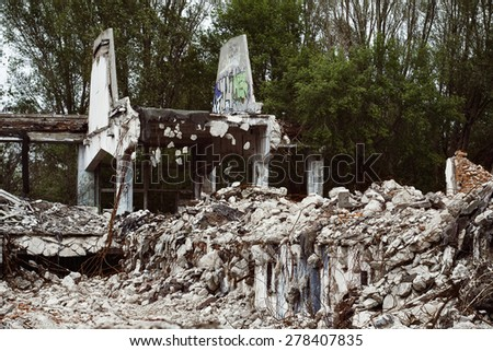 Ruined building of a factory with concrete hanging on armature and trees at background. Concept of disaster, war - stock photo