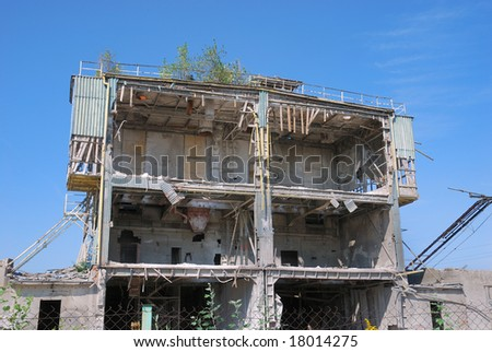 Ruined building without front walls. Blue sky background