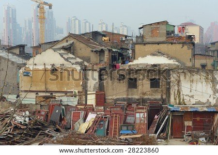 Ruined old buildings in foreground. People still living there. Modern city in background - stock photo