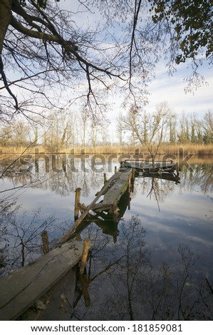 Ruined pier resting at sunny morning with reflection - stock photo