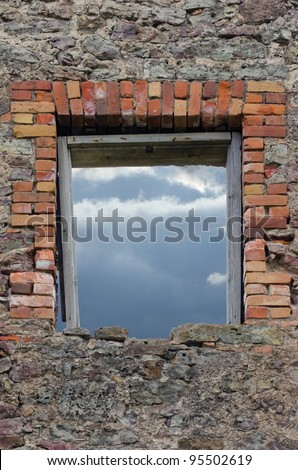Ruined rustic limestone boulder rubble wall masonry stonework ruins and red brick window aperture opening with weathered old aged wooden frame showing cloudy sky - stock photo