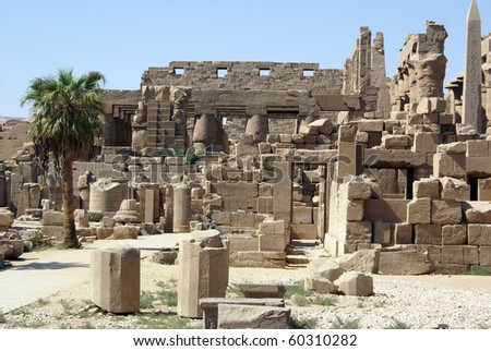 Ruins and palm trees in Karnak temple in Luxor, Egypt - stock photo