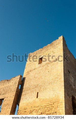 Ruins of a medieval fortress against sunny sky - stock photo