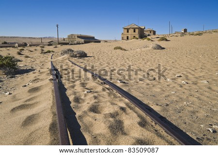 Ruins of abandoned houses and the old rail track in the ghost diamond town Kolmanskop near Lüderitz, Namibia, Africa - stock photo