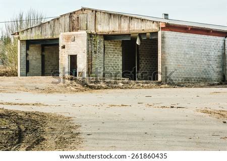Ruins of an old industrial building with grey bricks and no doors. Building has been a drive through service hall for vehicles. Only roof and walls still present. - stock photo