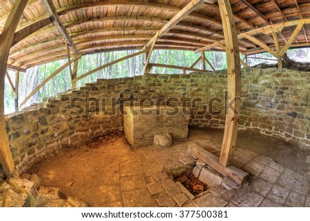 Ruins of ancient fortress covered with wooden roof in fish-eye perspective