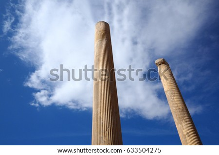 Ruins of Apadana and Tachara Palace behind stairway with bas relief carvings in Persepolis UNESCO World Heritage Site against cloudy blue sky in Shiraz city of Iran.