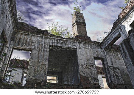 Ruins of shabby building covered by vegetation and mysterious sky. There are a lot of vegetation on the brick walls of derelict building. Photo was made in a distant town of Far East in Russia. - stock photo