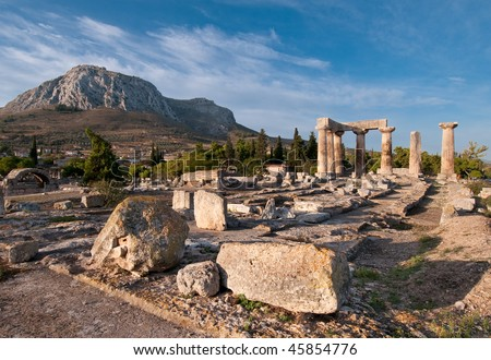Ruins of Temple of Apollo, Ancient Corinth, Greece with hill fortress of Acrocorinth in background - stock photo